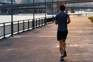Guy Running Along River in City